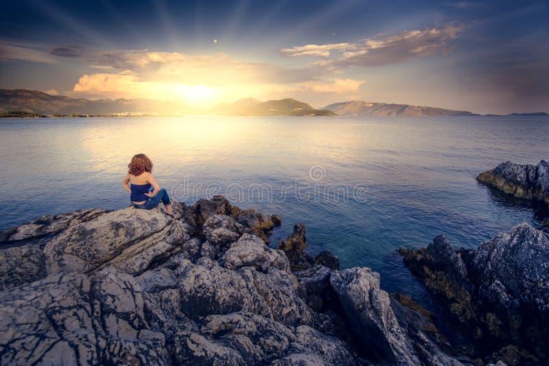 Jovem mulher que senta-se pelo mar Mediterrâneo azul imagem de stock royalty free