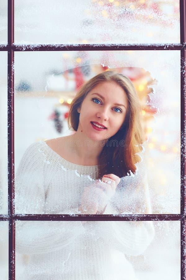 Jovem mulher que senta-se perto da janela no dia de inverno nevado imagem de stock