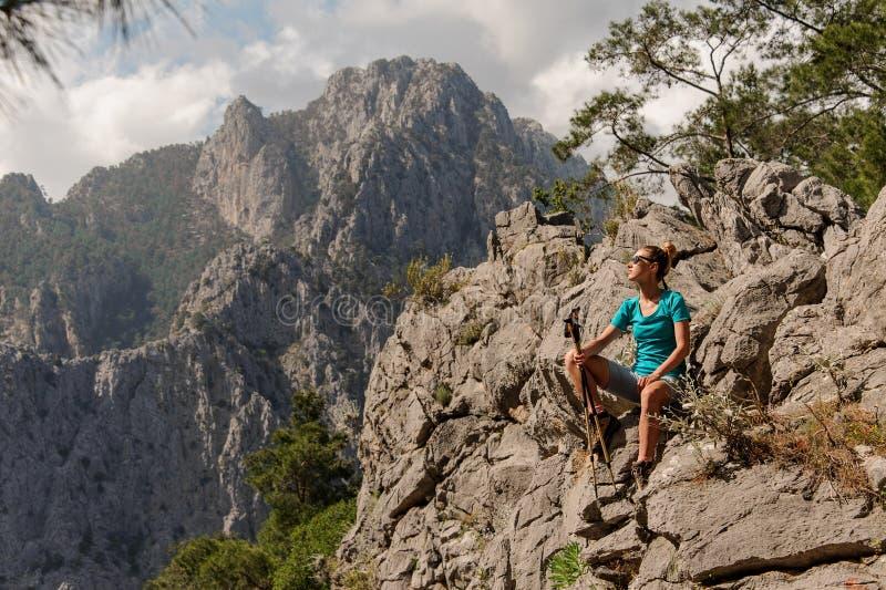 Jovem mulher que senta-se sobre a montanha foto de stock