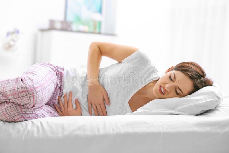Jovem mulher que sofre da dor abdominal fotos de stock royalty free