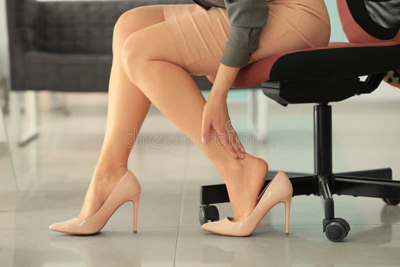 Jovem mulher que sofre da dor de pé devido às sapatas incômodas ao sentar-se no sofá fotos de stock
