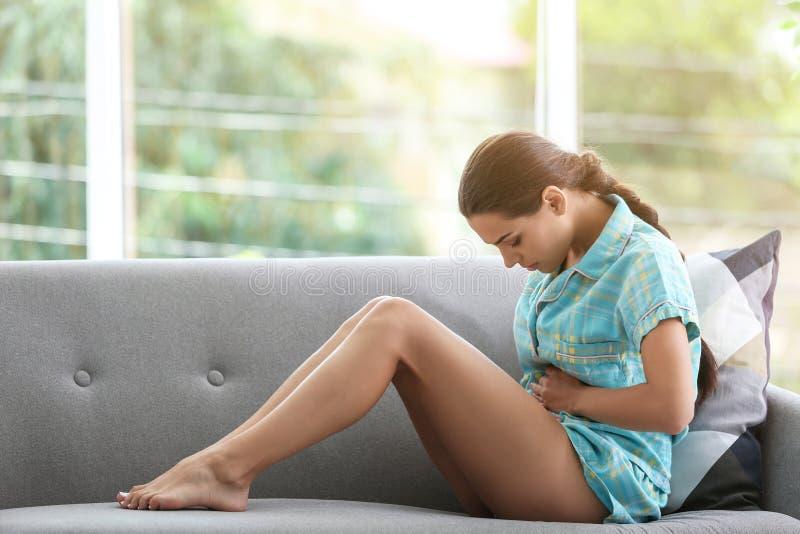 Jovem mulher que sofre dos grampos menstruais imagens de stock royalty free