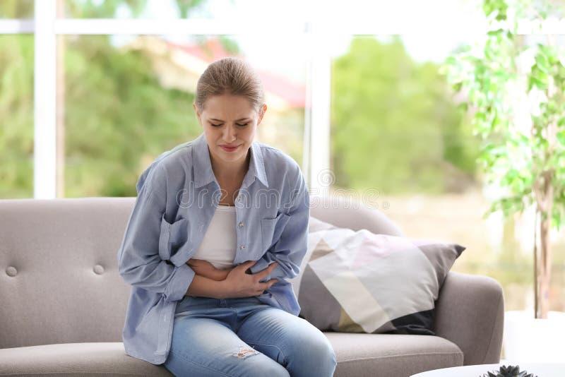 Jovem mulher que sofre dos grampos menstruais fotos de stock