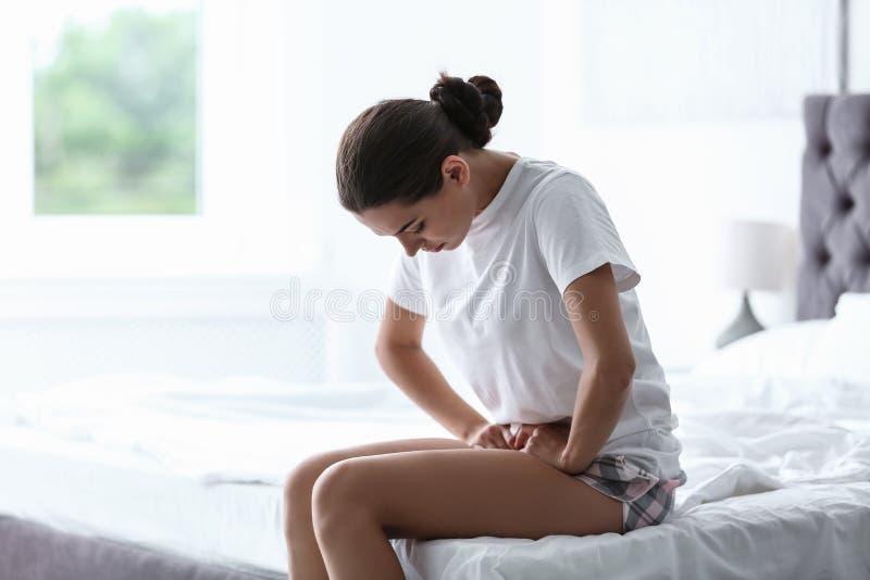 Jovem mulher que sofre dos grampos menstruais fotografia de stock royalty free