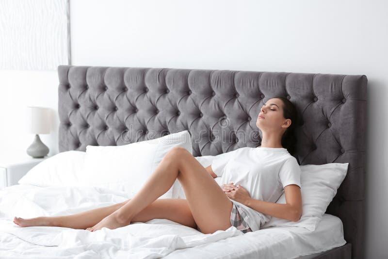 Jovem mulher que sofre dos grampos menstruais em casa imagens de stock