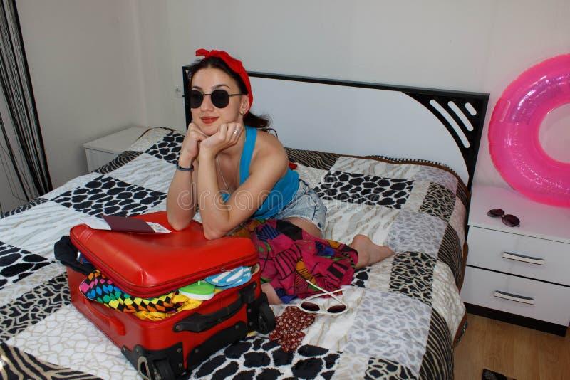 A jovem mulher que sonha de uma viagem do mundo senta-se perto da mala de viagem aberta foto de stock royalty free