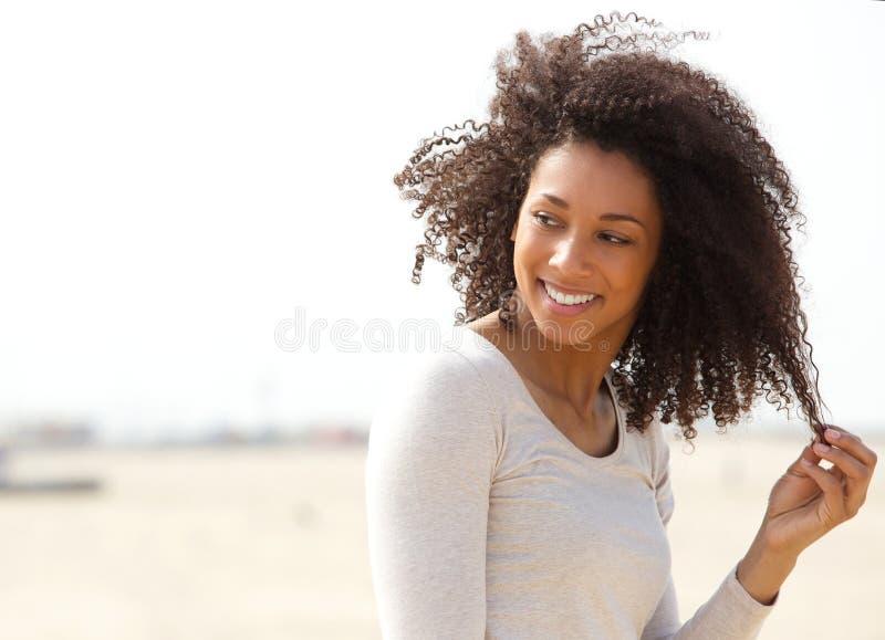 Jovem mulher que sorri com cabelo encaracolado imagem de stock