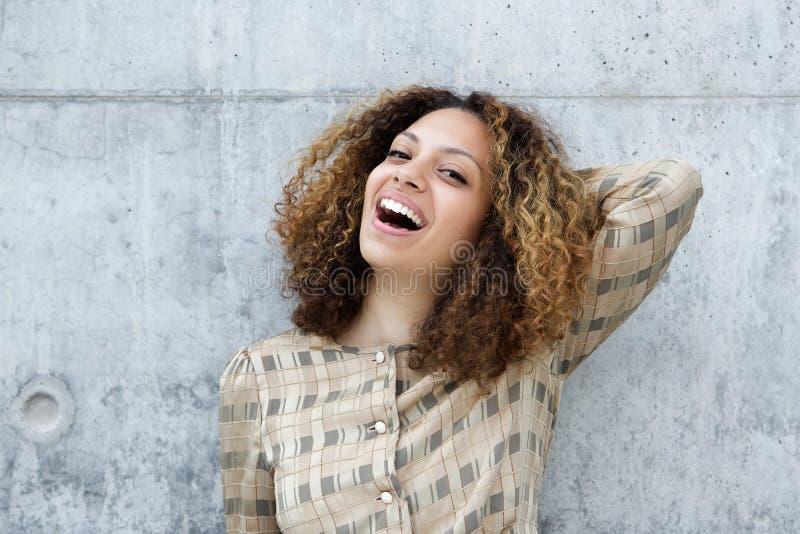 Jovem mulher que sorri com mão no cabelo fotografia de stock