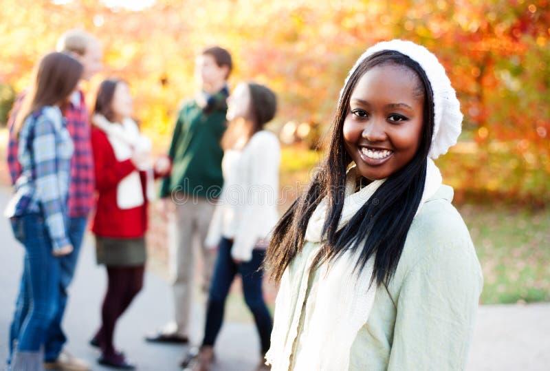 Jovem mulher que sorri com os amigos no fundo foto de stock