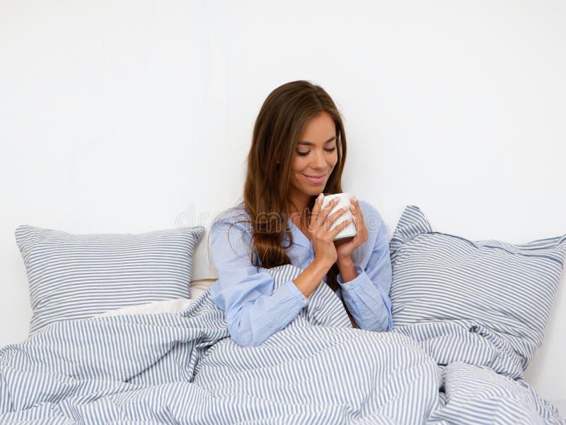 Jovem mulher que sorri com xícara de café imagens de stock royalty free