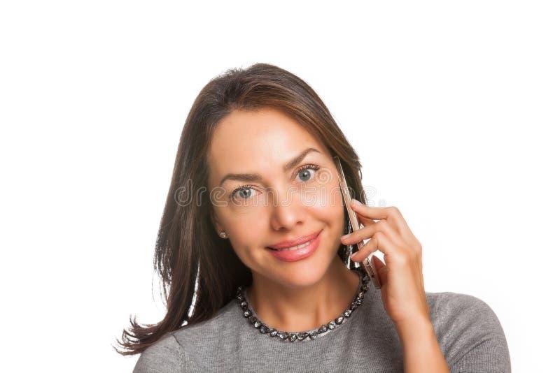 Jovem mulher que sorri e que fala em seu telefone celular isolado fotografia de stock royalty free