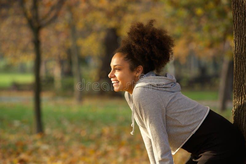Jovem mulher que sorri e que descansa após o exercício no parque fotografia de stock royalty free