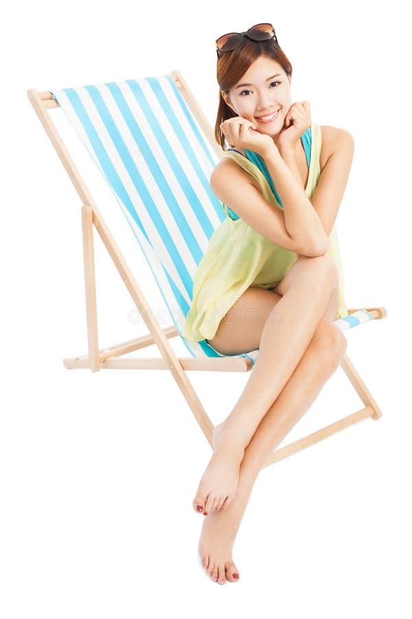 Jovem mulher que sorri e que senta-se em uma cadeira de praia foto de stock