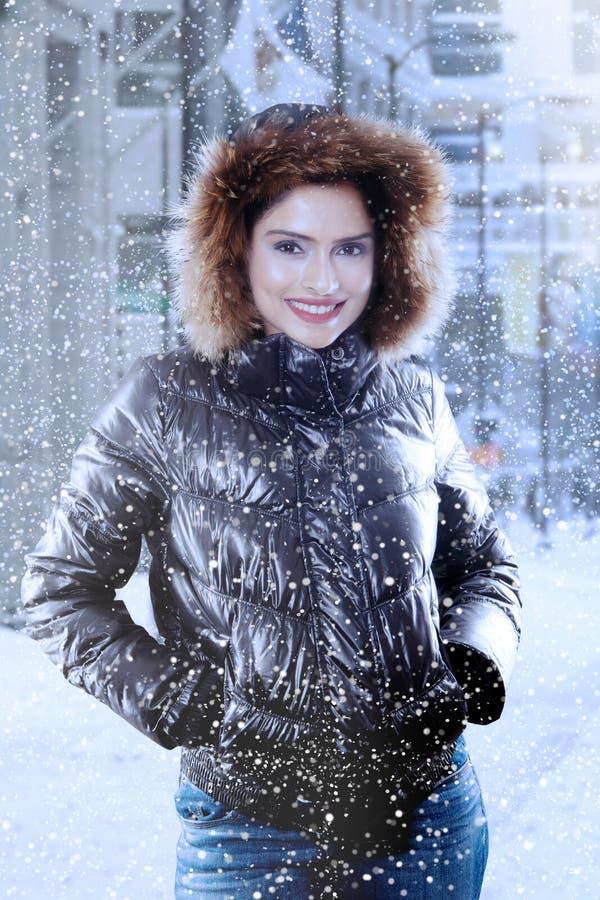 Jovem mulher que sorri sob a queda de neve foto de stock royalty free