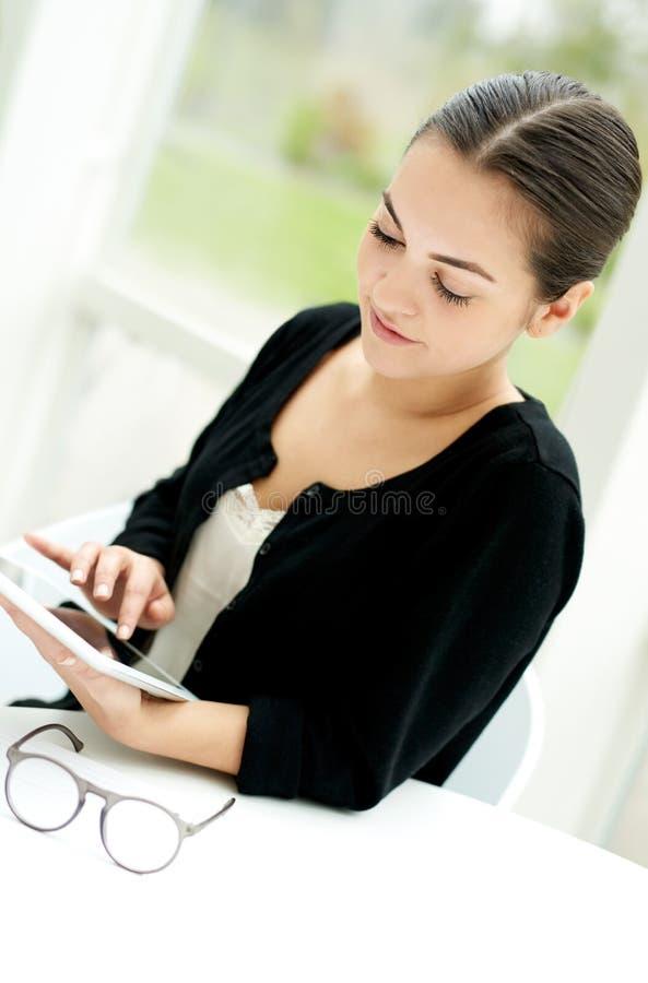 Jovem mulher que surfa em um tabuleta-PC foto de stock royalty free