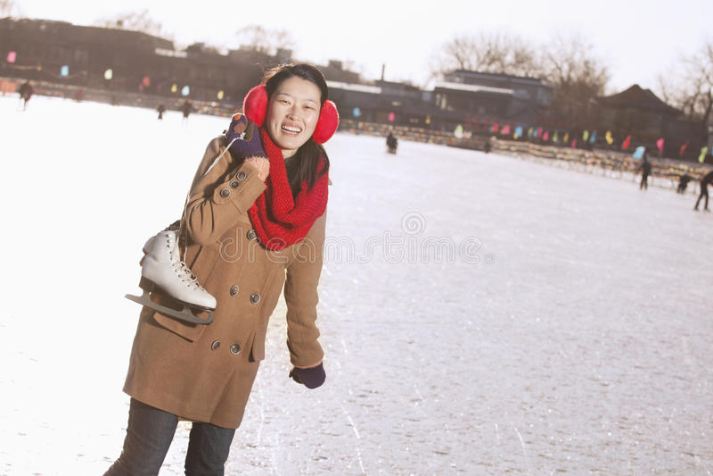Jovem mulher que sustenta patins de gelo fora, Pequim imagem de stock