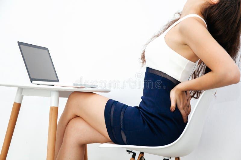 Jovem mulher que tem a dor nas costas/dor lombar/síndrome crônicas do escritório ao trabalhar com o portátil na mesa branca fotografia de stock royalty free