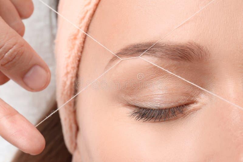 Jovem mulher que tem o procedimento da correção da sobrancelha foto de stock