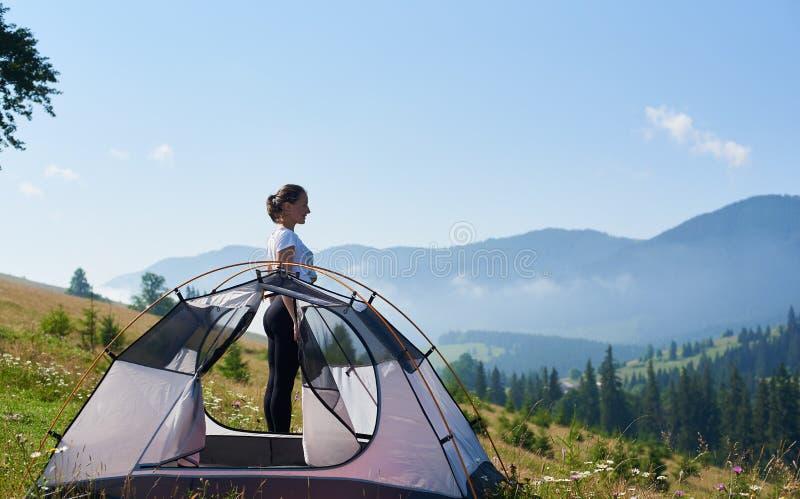 Jovem mulher que tem um resto perto da barraca do turista na manhã do verão nas montanhas foto de stock