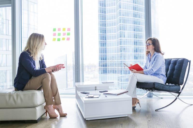 Jovem mulher que tem uma entrevista de trabalho com um gerente de aluguer fotos de stock royalty free