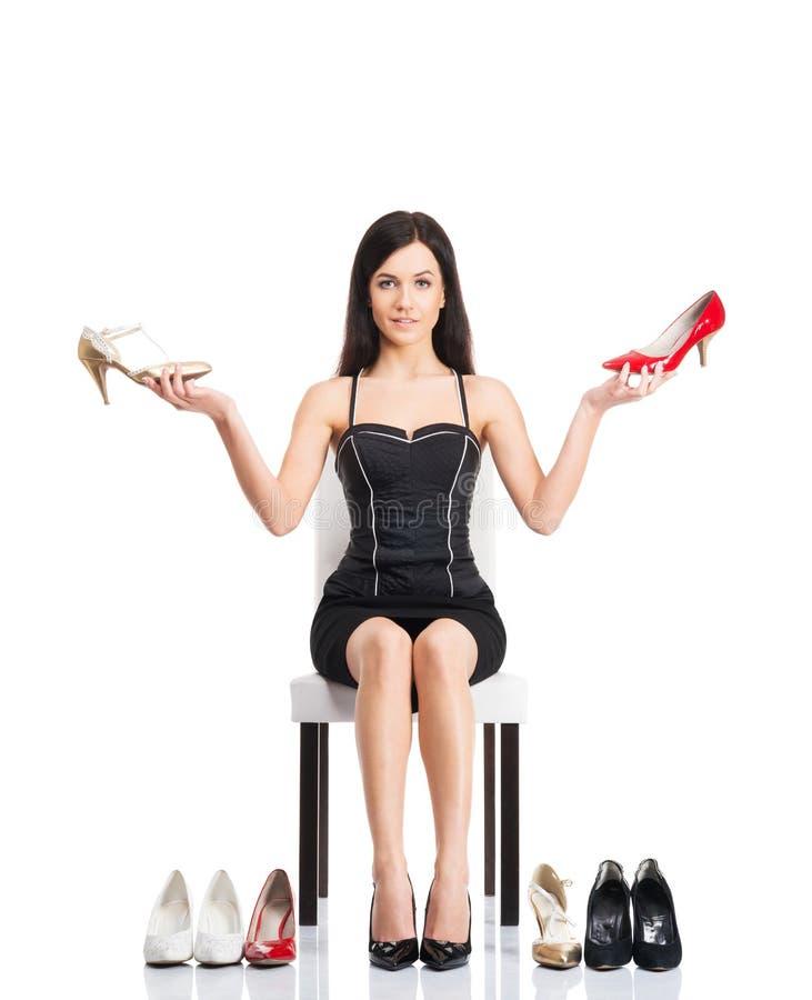 Jovem mulher que tenta escolher os calçados direitos fotos de stock royalty free