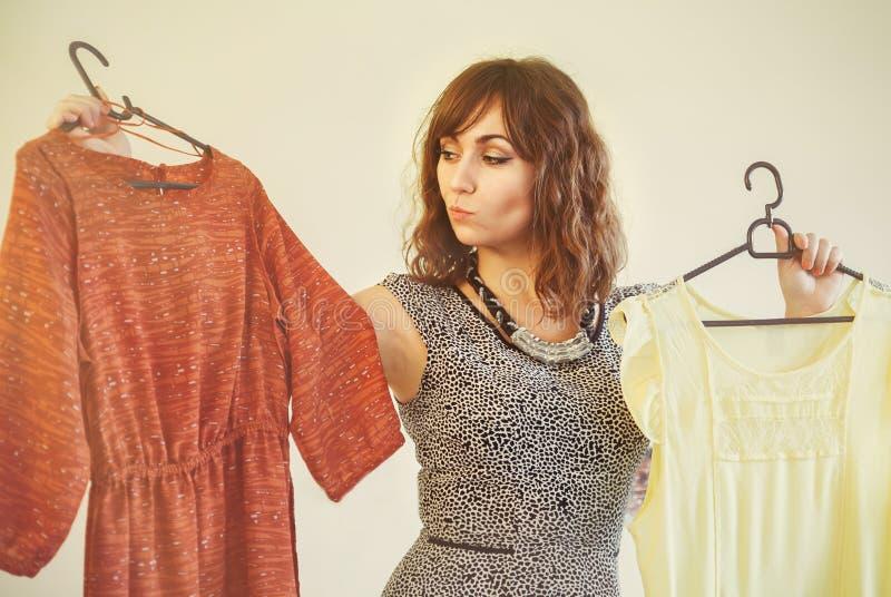Jovem mulher que tenta escolher um vestido vestir imagens de stock
