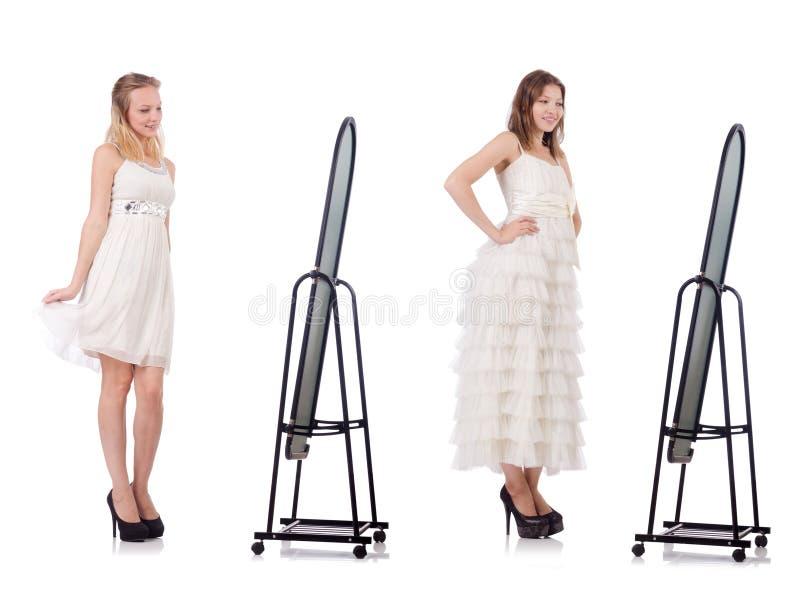 A jovem mulher que tenta o vestido novo na frente do espelho fotografia de stock
