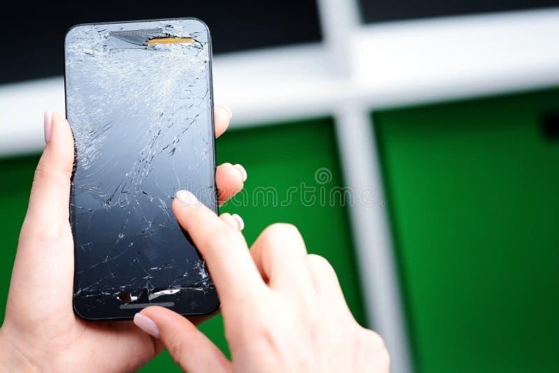 Jovem mulher que tenta usar um telefone celular de vidro quebrado imagem de stock royalty free