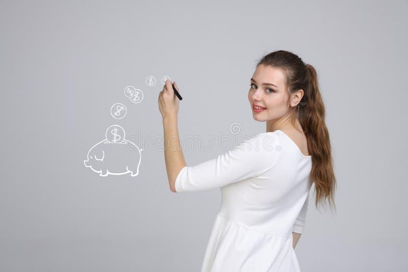Jovem mulher que tira um mealheiro fotografia de stock