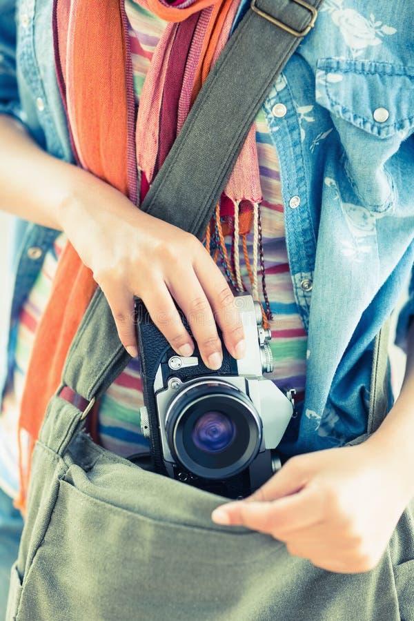 Jovem mulher que toma a câmera de seu saco fotografia de stock