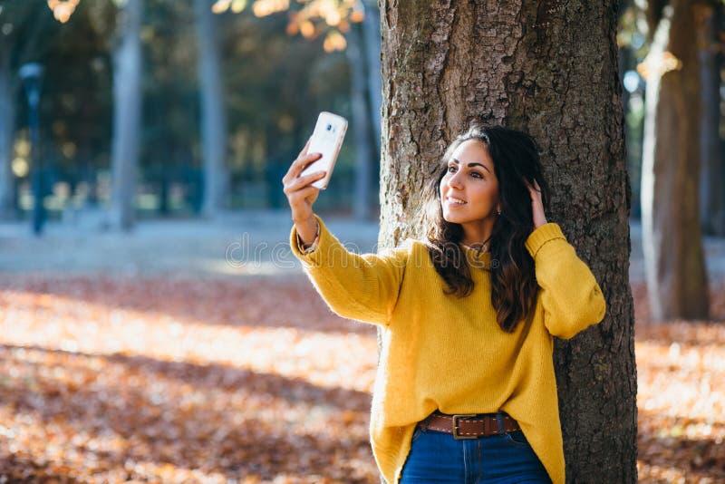 Jovem mulher que toma a foto do selfie com o telefone esperto no outono fotos de stock