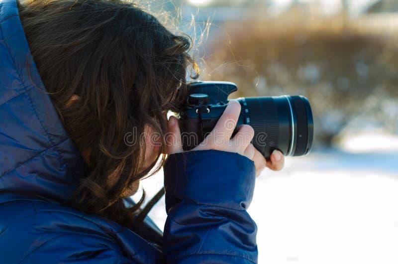 Jovem mulher que toma a foto exterior no inverno foto de stock royalty free