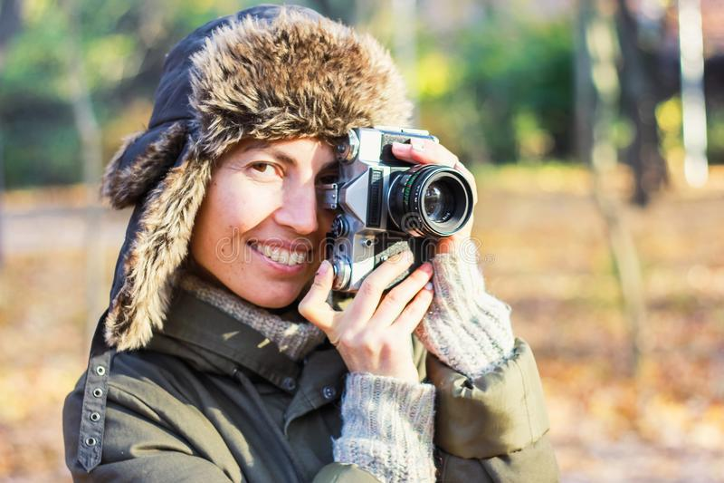 Jovem mulher que toma imagens no parque do outono imagem de stock