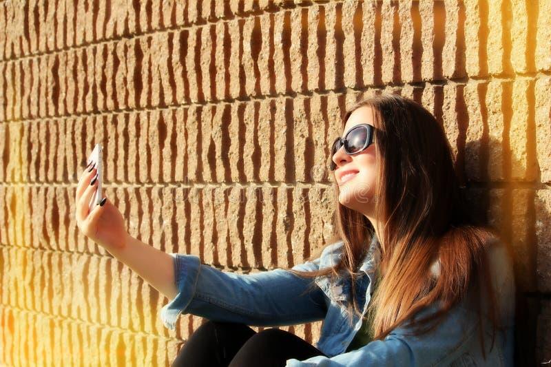 Jovem mulher que toma o selfie na frente de uma parede de tijolo imagens de stock royalty free