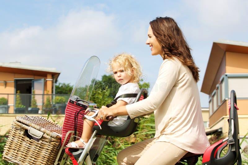 Jovem mulher que toma sua filha no passeio da bicicleta foto de stock royalty free