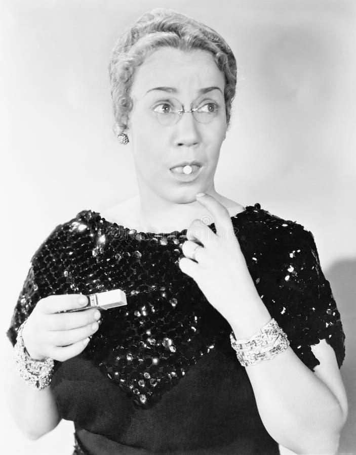 Jovem mulher que toma um comprimido em sua boca (todas as pessoas descritas não são umas vivas mais longo e nenhuma propriedade e fotografia de stock