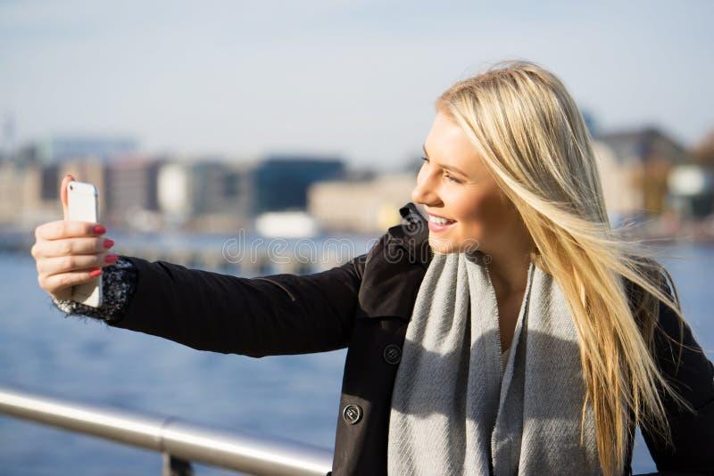 Jovem mulher que toma um selfie no sol imagens de stock