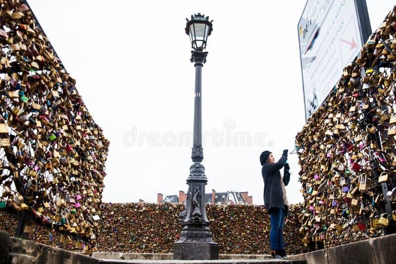 A jovem mulher que toma uma imagem do amor trava em Pont Neuf em Paris fotos de stock royalty free