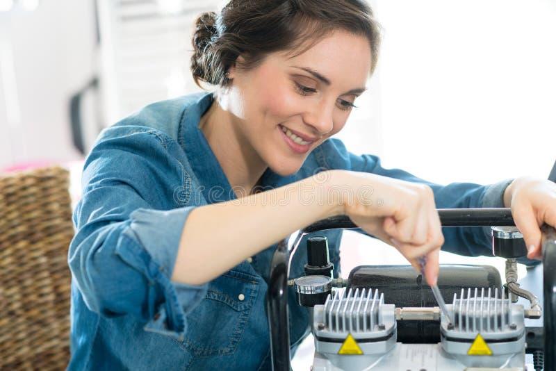 Jovem mulher que trabalha com bateria imagem de stock