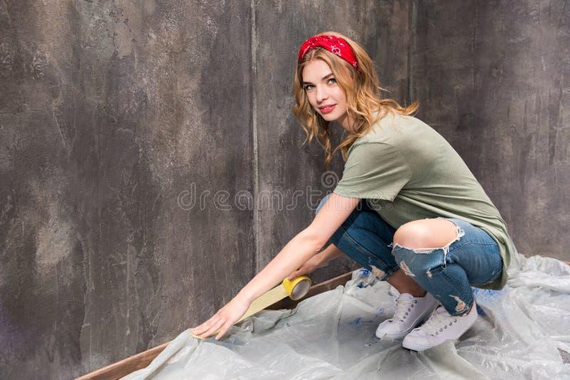 Jovem mulher que trabalha com fita e que prepara a sala para a casa da renovação fotografia de stock royalty free