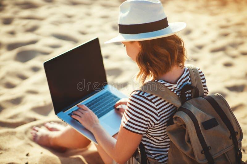 Jovem mulher que trabalha com o port?til na natureza na praia fotografia de stock