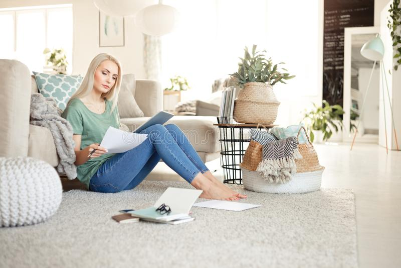 Jovem mulher que trabalha em casa, sentando-se no assoalho na sala de visitas foto de stock