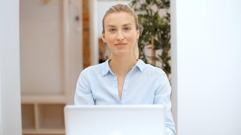 Jovem mulher que trabalha em seu laptop e que usa o smartphone em casa foto de stock