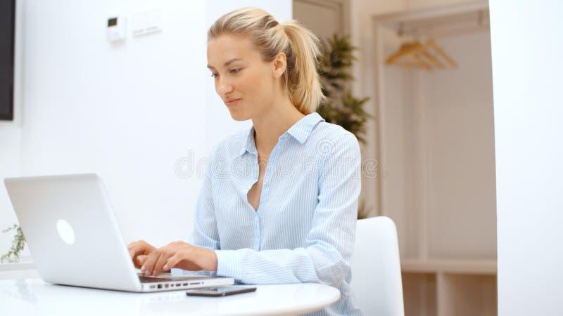 Jovem mulher que trabalha em seu laptop e que usa o smartphone em casa fotografia de stock