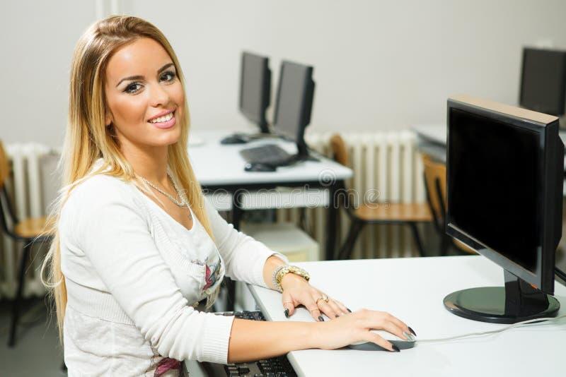Jovem mulher que trabalha em um computador na sala de aula fotografia de stock royalty free