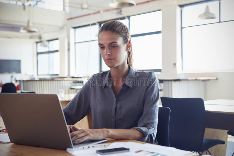 Jovem mulher que trabalha em um escritório usando um laptop foto de stock