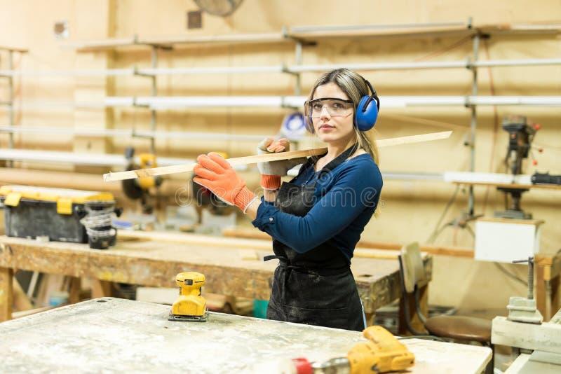 Jovem mulher que trabalha em um woodshop fotos de stock royalty free