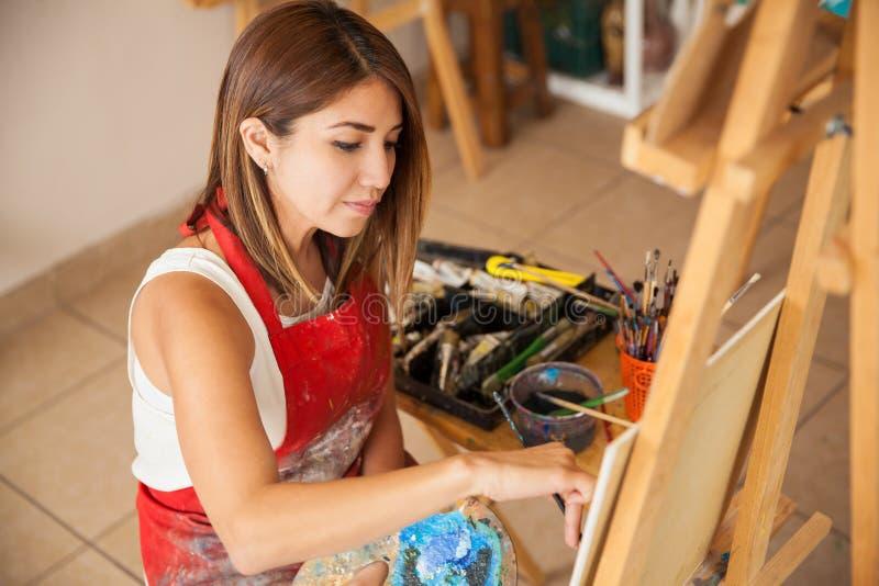 Jovem mulher que trabalha em uma pintura imagens de stock