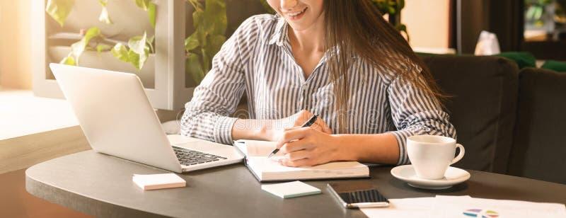 Jovem mulher que trabalha no café, artigo de datilografia no portátil fotografia de stock royalty free