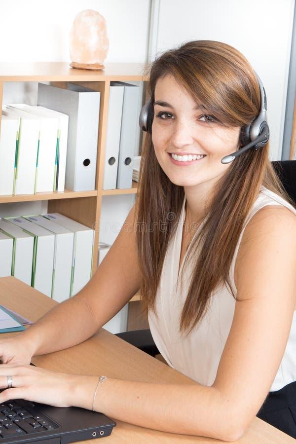 Jovem mulher que trabalha no callcenter usando auriculares fotos de stock